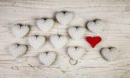 Jeden czerwony serce w kolekci wiele biali serca na drewnianym sha Fotografia Stock