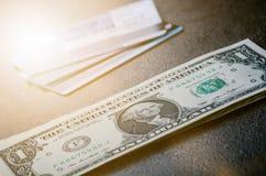 Jeden dolara banknoty na czarnym stole z kredytowymi kartami Gotówkowi pieniądze amerykanina dolary ornamentu geometryczne tła ks Zdjęcia Stock