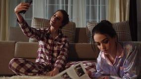 Jeden dwa ładnej siostry robi selfie na smartphone przy wieczór podczas gdy inny czytelniczy magazyn w wygodnym żywym pokoju zbiory