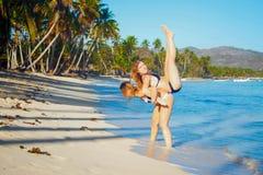 Jeden dziewczyna trzyma innej dziewczyny na plecy na tropikalnym seashore z wysokimi drzewkami palmowymi obraz royalty free