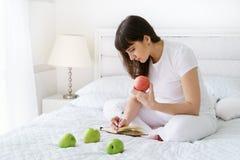 Jeden europejski kobieta w ciąży jest pisać niektóre pomysle i myśleć w notatniku piórem w białej sypialni przy dnia czasem Zdjęcia Royalty Free
