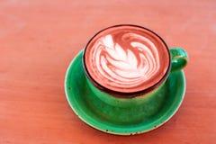 Jeden filiżanka cappuccino z latte sztuką Żywy Koralowy kolor na drewnianym tle, greenery ceramiczna filiżanka, miejsce dla tekst zdjęcia royalty free