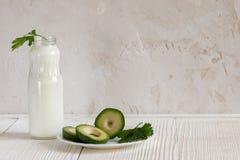 Jeden folował rozpieczętowaną butelkę kefir, zielona pietruszka i avocado plasterki na białym tle z kopii przestrzenią, zdjęcia royalty free