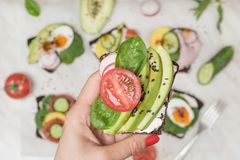 Jeden kanapka z świeżym lato pomidorem, avocado w żeńskiej ręce i z bliska Obraz Royalty Free