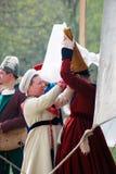 Jeden kobieta pomaga inny stawiać kapelusz dalej Zdjęcie Royalty Free
