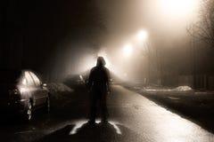 Jeden mężczyzna na mgłowej ulicie przy nocą Obrazy Stock