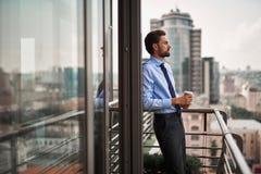 Jeden męski pracownik pije kawę na biurowym balkonie zdjęcia royalty free
