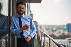 Jeden męski pracownik pije kawę na biurowym balkonie zdjęcia stock