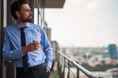 Jeden męski pracownik pije kawę na biurowym balkonie obraz royalty free