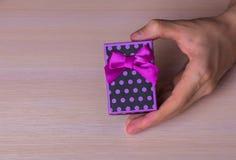 Jeden męskich ręki mienia purpur prezenta łaciasty pudełko Obraz Royalty Free