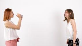 Jeden młoda kobieta filmuje inny nad białą ścianą zbiory