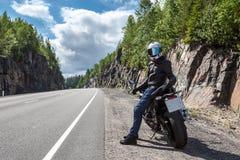 Jeden motortraveler z swój motocyklem odpoczywa na poboczu na halnej asfaltowej drodze obraz royalty free