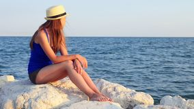 Jeden nastoletnia dziewczyna siedzi samotnie na skały morza plaży w lato wieczór w Panama zdjęcie wideo