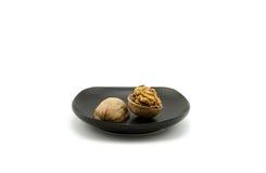 Jeden orzech włoski skorupy łamanie w czarnym talerzu Zdjęcie Stock