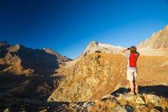 Jeden osoba patrzeje widok wysokiego up na Alps Expasive krajobraz, idylliczny widok przy zmierzchem odosobniony tylni widok biel fotografia stock