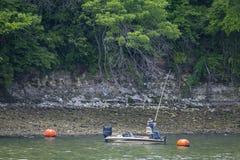 Jeden osoba połów w outboard silnika łodzi rybackiej blisko bouys pod wysokim bulwarem z udziałami bardzo zieleni drzewa up wysok obrazy stock