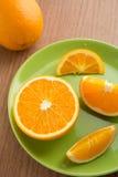 Jeden pomarańcze i plasterki pomarańcze na talerzu Fotografia Stock