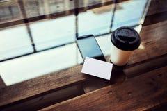 Jeden Pusty Białego papieru wizytówki Mockup drewna stół Bierze Oddalonego filiżanki Coworking studio Nowożytny telefon pracy biu obraz stock