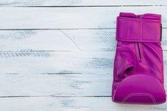 Jeden różowa bokserska rękawiczka na białej drewnianej powierzchni Fotografia Stock