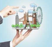 Jeden ręka trzyma pastylkę z patroszonego holograma turystycznymi miejscami, inni ręka punkty out piękni turystyczni miejsca Prze Obraz Royalty Free