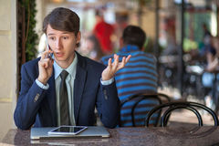 Jeden relaksował młodego przystojnego fachowego biznesmena pracuje z laptopem, telefonem i pastylką w hałaśliwie kawiarni jego, zdjęcia royalty free