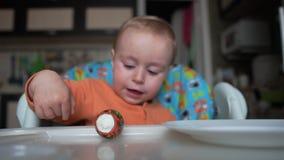 Jeden roczniak chłopiec siedzi i sztuka z Easter jajkami w zwolnionym tempie zbiory