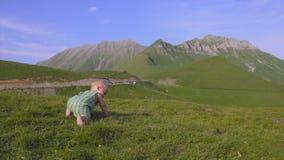 Jeden roczniak chłopiec uczy się chodzić na tle góry zdjęcie wideo