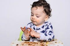 Jeden roczniaka dzieciak je plasterek urodzinowy roztrzaskanie tort on dostaje brudny Zdjęcie Stock