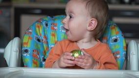 Jeden roczniaka dziecko siedzi w sztukach z Easter jajkiem i kuchni - zwolnione tempo zbiory
