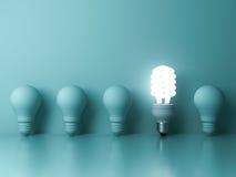 Jeden rozjarzony ścisły fluorescencyjny lightbulb stoi out od unlit płonącego żarówki odbicia na zielonym tle Zdjęcie Royalty Free