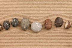 Jeden rząd kamienie kłama na piasku z przestrzenią dla teksta, Fotografia Stock