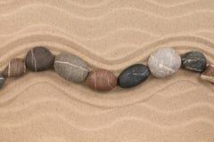 Jeden rząd kamienie kłama na piasku z przestrzenią dla teksta, Obrazy Stock
