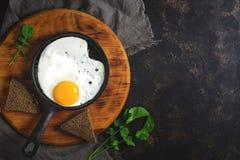 Jeden smażący jajko w małej smaży niecce Ciemny nieociosany tło, odgórny widok, kopii przestrzeń obrazy royalty free