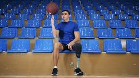 Jeden sportowiec z protetyczną nogą trzyma piłkę w rękach, zakończenie w górę zbiory