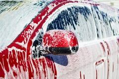 Jeden strona czerwony samochód jest wszystko w pianie na samochodowym obmyciu, stosuje kontakt pianę maszyny obraz stock