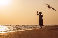 Jeden szczęśliwa chłopiec bawić się na plaży przy zmierzchu czasem Fotografia Royalty Free