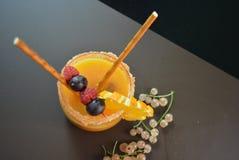 Jeden szkło z sok pomarańczowy owoc, malinki, rodzynek, czernica, pomarańcze, agrest, słoma, sahor na brown matte tle Zdjęcia Stock