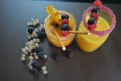 Jeden szkło z sok pomarańczowy owoc, malinki, rodzynek, czernica, pomarańcze, agrest, słoma, sahor na brown matte tle Fotografia Stock
