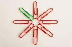 Jeden zielona klamerka w grupie czerwone klamerki Fotografia Royalty Free