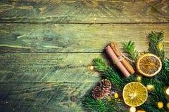 Jedlinowy cynamon susząca gałąź pomarańcze pokrajać sosnowych rożki na starym deski drewna tle złoci bokeh światła boże narodzeni zdjęcia royalty free