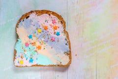 Jednorożec jedzenie wznosił toast chleb z colorfur kremowym serem Zdjęcia Stock