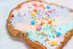 Jednorożec jedzenie wznosił toast chleb z colorfur kremowym serem Obraz Stock