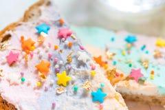 Jednorożec jedzenie wznosił toast chleb z colorfur kremowym serem Fotografia Stock