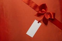 Jedwabniczej tkaniny tło, Czerwony Atłasowy Tasiemkowy łęk, metka Zdjęcia Royalty Free