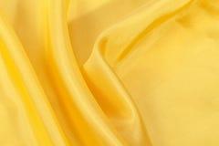 Jedwabniczy tło, tekstura żółta błyszcząca tkanina Obraz Royalty Free