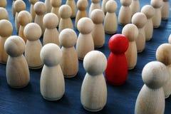 Jedyność, indywidualność i różnica, Czerwona drewniana postać w tłumu obraz royalty free