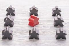 Jedyność, indywidualność i różnica, Czerwona drewniana postać w tłumu różny kolor zdjęcie royalty free