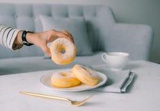 Jedzenie i piekarnia, ręka Trzyma Wyśmienicie Świeżych i Słodkich pączków wi fotografia royalty free