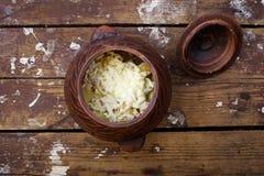 Jedzenie w glinianym garnku na drewnianym tle Wieśniaka stylowy jedzenie zdjęcie stock