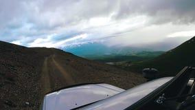 Jedzie samochód ciężkiego na chmurnym dniu Auto podróż: POV - punkt widzenia SUV jedzie dolinę z górami w zbiory wideo
